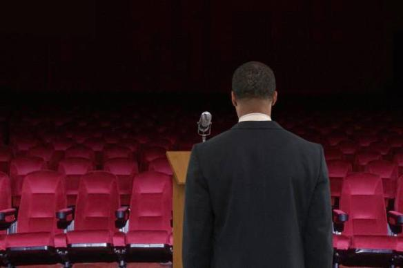 Mixed race businessman at podium in empty auditorium